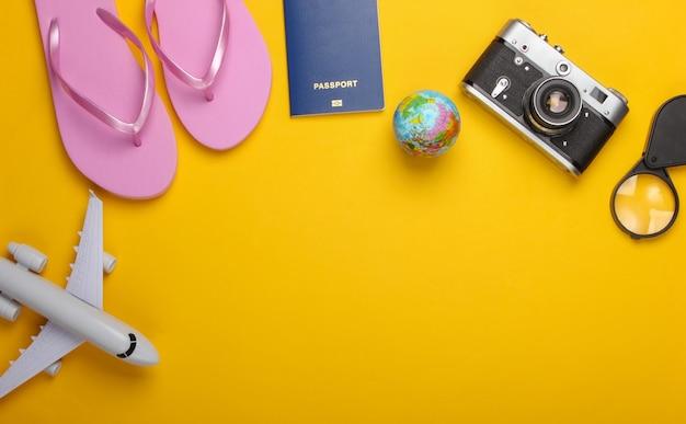 Sommerstrand und reiseaccessoires auf gelber wand tourismuswand flach legen. draufsicht. speicherplatz kopieren