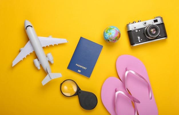 Sommerstrand und reiseaccessoires auf gelber wand tourismuswand flach legen. draufsicht