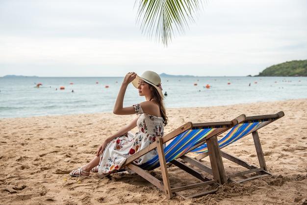 Sommerstrandferien-feiertagsreisekonzept, glückliche junge asiatin mit dem hut, der sich oben auf strandstuhl und angehobenen händen entspannt.