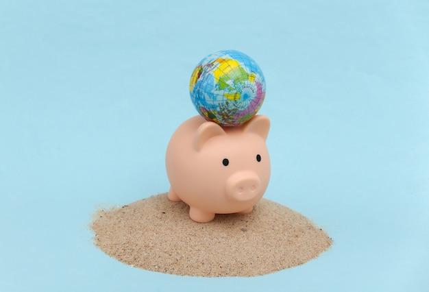 Sommerstrandreise-urlaubskonzept. sparschwein und globus auf einer insel mit sand