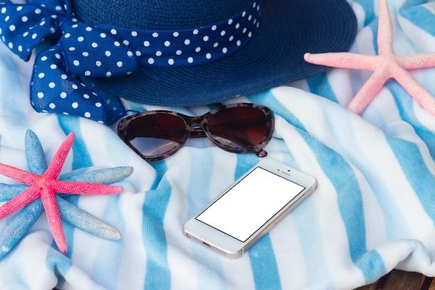 Sommerstrandtuch, seestern, sonnenbrille und hut, kopienraum auf dem telefon mit leerem bildschirm