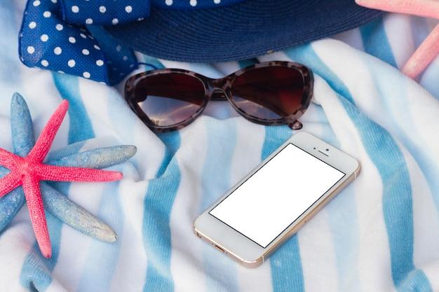 Sommerstrandtuch, seestern und hut, kopienraum auf dem telefon mit leerem bildschirm