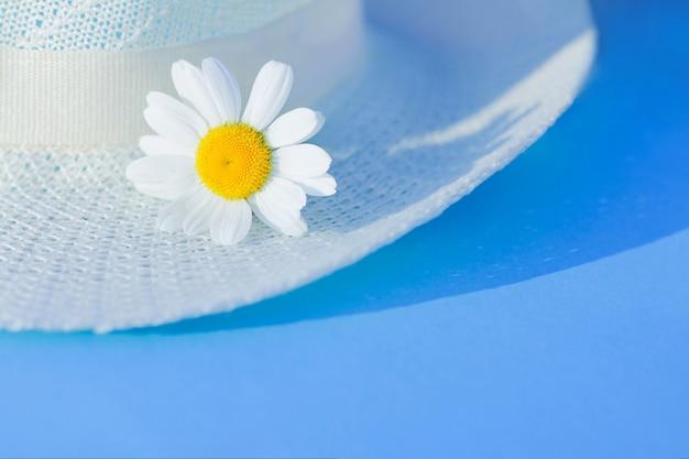 Sommerstrohhut und gänseblümchenblumen auf blauem tisch. sommersaison, urlaub, wochenend-entspannungskonzept