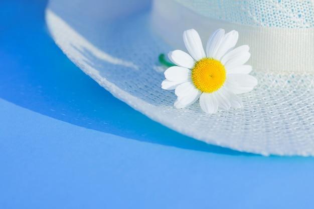Sommerstrohhut und gänseblümchenblumen. sommersaison, urlaub, wochenend-entspannungskonzept