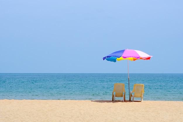 Sommerstuhl und bunter regenschirm auf strand und meer mit copyspace