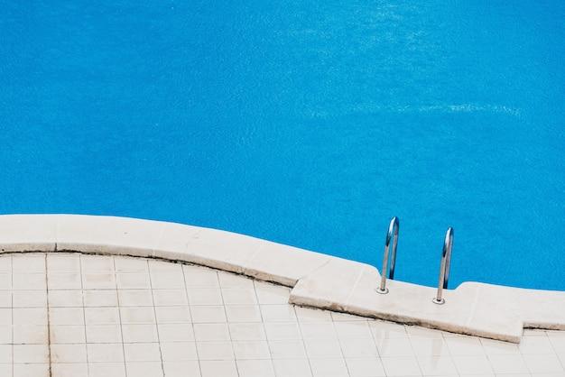 Sommersturm, ein feiner regen fällt auf das blaue wasser eines schwimmbades in einem hotel.