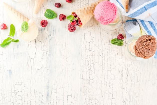 Sommersüße beeren und desserts, verschiedene eissorten in zapfenrosa (himbeere), vanille und schokolade mit minze auf leichtbeton