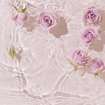 Sommerszene mit rosa rosenblüten im wasser.