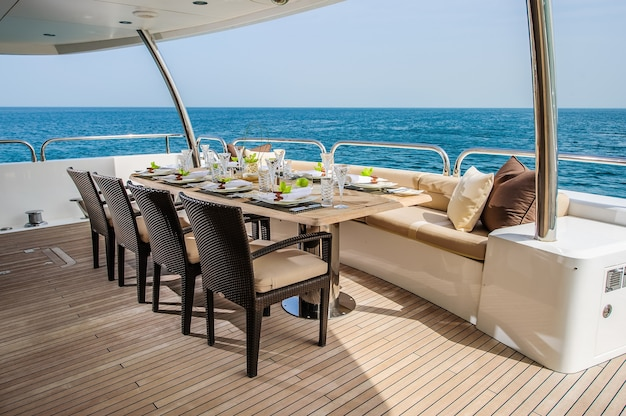 Sommertag yachtdeck mit serviertem tisch und offenem meer.