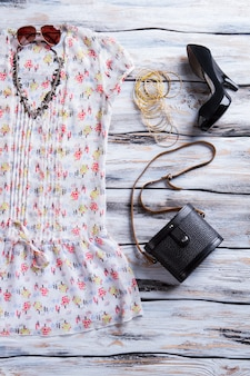 Sommertop mit dunklen absätzen. absatzschuhe, top und armbänder. trendiges outfit für damen. verkauf von kleidung in boutique.