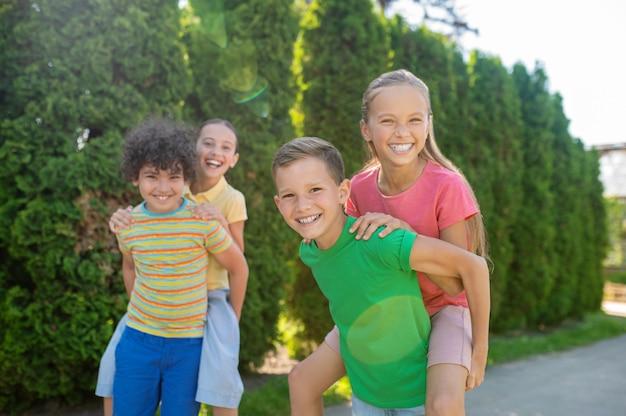 Sommerurlaub. fröhliche begrüßung von freunden im grundschulalter, die aktiv die sommerferien im grünen park verbringen
