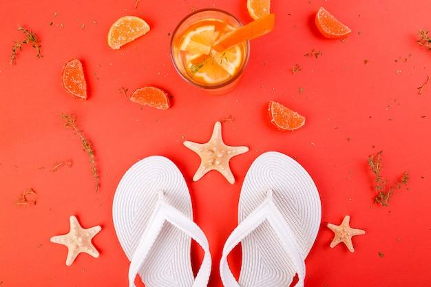Sommerurlaub. orange fruchtcocktail, detoxwasser nahe weißen flipflops.
