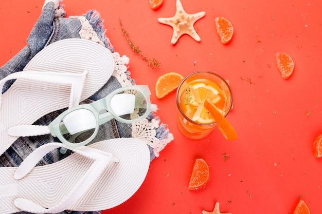 Sommerurlaub. orangenfruchtcocktail, detoxwasser in der nähe von weißen flipflops, shorts und sonnenbrillen.