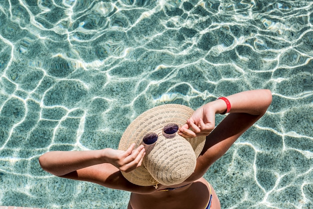 Sommerurlaub. schöne frau, die neben einem pool liegt.