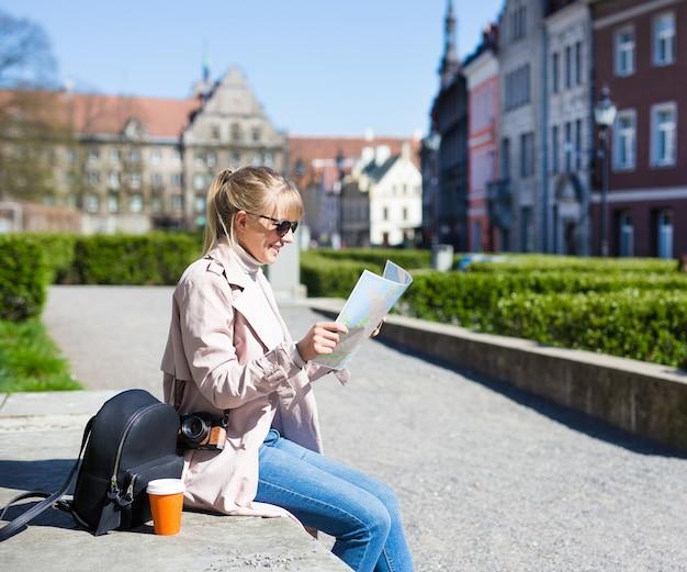 Sommerurlaub und reisekonzept - glückliche frau mit sonnenbrille mit karte, rucksack und kamera in der altstadt von tallinn, estland