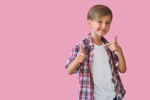 Sommerurlaub und urlaubskonzept. fröhlicher, stilvoller schuljunge in gelber sonnenbrille mit daumen nach oben vor rosafarbenem hintergrund. zurück zur schule