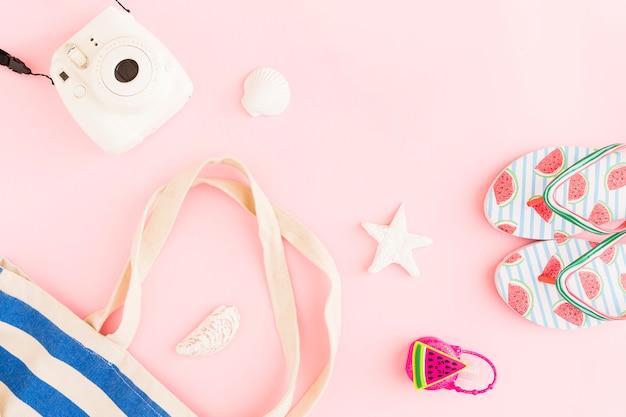 Sommerurlaubsortensachen auf rosa hintergrund
