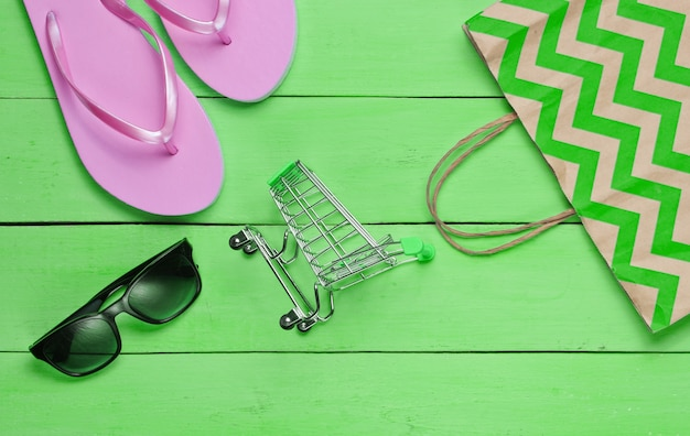 Sommerverkauf. shopping-konzept. sommerstrandzubehör (flip-flops, sonnenbrille), mini-einkaufswagen auf grünem holzhintergrund. ansicht von oben. flach legen