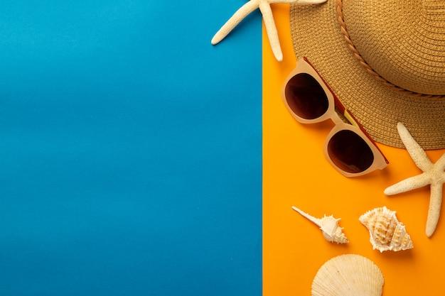 Sommerwand mit strandaccessoires - strohhut, sonnenbrille auf lebendiger orange und blauer wand draufsicht mit kopierraum