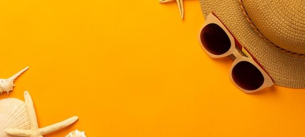 Sommerwand mit strandzubehör - strohhut, sonnenbrille auf lebendiger orangefarbener bannerwand draufsicht mit kopierraum