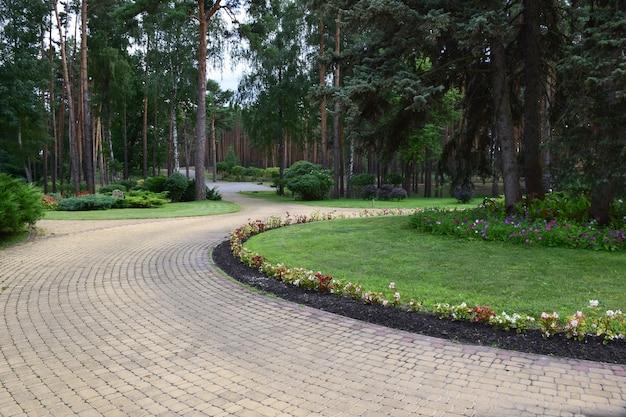 Sommerweg im park, gesäumt von pflastersteinen. blumen und büsche wachsen an den seiten