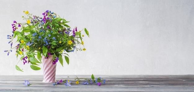 Sommerwildblumen in der rosa keramikvase auf weißer oberfläche