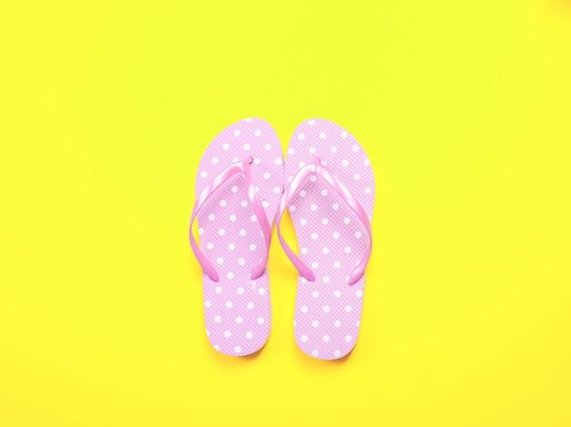 Sommerwohnung lag. rosa flipflops und sonnenbrille des strandzubehörs auf gelbem hintergrund.