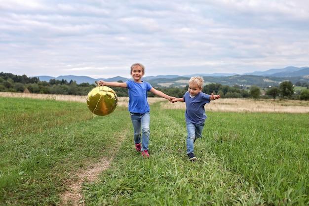 Sommerzeit nach dem lockdown. kinder laufen zusammen auf der wiese in den bergen, neue normalität