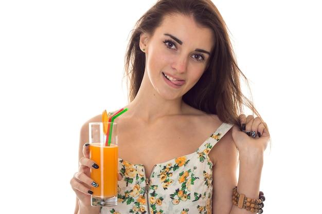Sommerzeit-nahaufnahmeporträt der jungen charmanten frau in den hellen kleidern mit cocktail in den händen, die lokal auf weißer wand aufwerfen