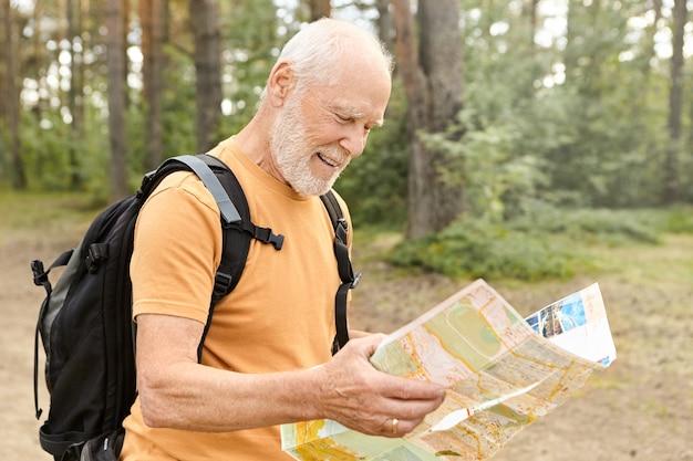 Sommerzeitbild des fröhlichen gutaussehenden energetischen reifen männlichen rentners mit weißem bart, der papierkarte hält, route studiert, während mit rucksack draußen allein in erstaunlichem wald, lächelnd