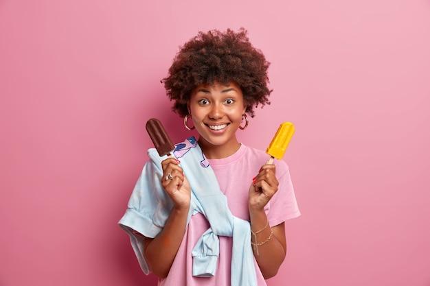 Sommerzeitkonzept. frohe positive frau mit afro-frisur hält leckeres gefrorenes eis, genießt es, leckeres kaltes dessert zu essen, lässig gekleidet, posiert