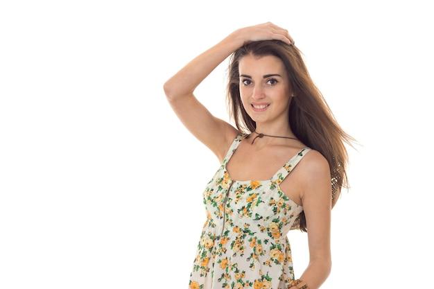 Sommerzeitporträt der jungen charmanten frau in den hellen kleidern, die isolierte weiße wand lächeln