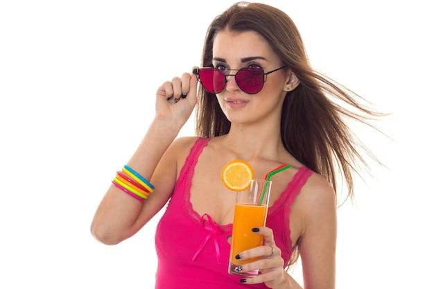 Sommerzeitporträt der jungen charmanten frau in der hellen kleidung und in der sonnenbrille mit cocktail in den händen, die lokal auf weißer wand aufwerfen