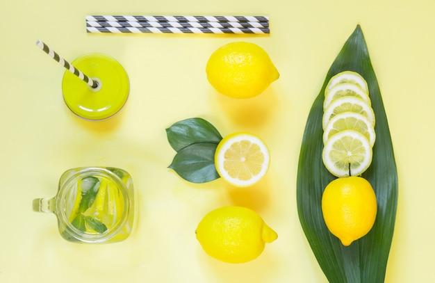 Sommerzitronenzusammensetzung für das kochen der detoxlimonade mit minze und eis im weckglas auf gelb.