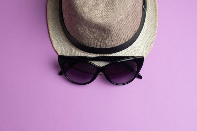 Sommerzubehör, hut und sonnenbrille auf rosa. sommerferien und seekonzept.