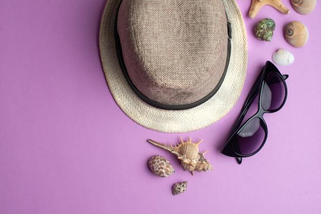 Sommerzubehör, oberteile, hut und sonnenbrille auf gelber oberfläche.