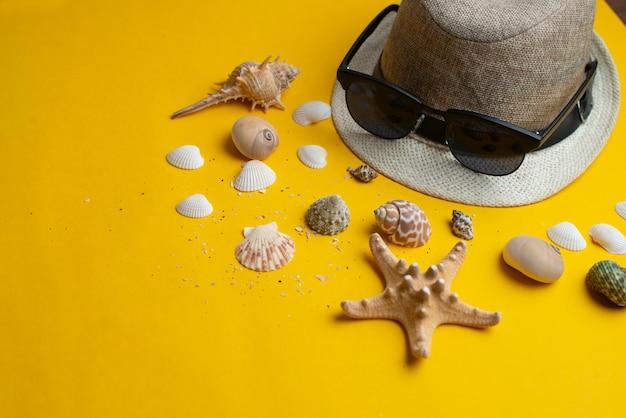 Sommerzubehör, oberteile, hut und sonnenbrillen auf gelb. sommer- und seekonzept.