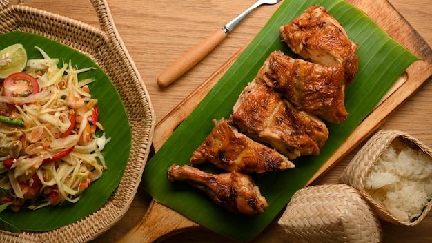 Somtum- oder papaya-salat mit gegrilltem hähnchen nach thailändischer art und klebreis traditionelles thai-essen