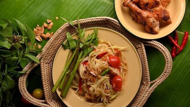 Somtum- oder papaya-salat mit gegrilltem hühnchen im thailändischen stil und gemüse auf bananenblättern hintergrund thailändisches essen