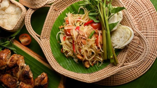 Somtum- oder papaya-salat mit gegrilltem hühnchen-klebreis und gemüse thailändisches traditionelles essen