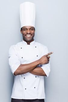 Sonderangebot vom küchenchef. selbstbewusster junger afrikanischer koch in weißer uniform, der weg zeigt und lächelt
