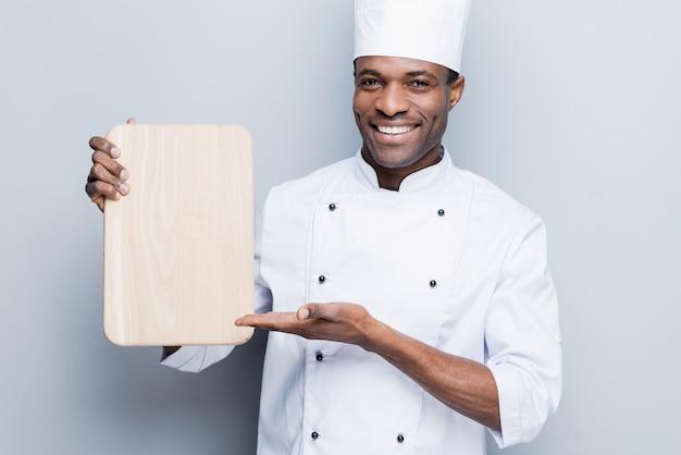 Sonderangebot vom küchenchef. selbstbewusster junger afrikanischer koch in weißer uniform