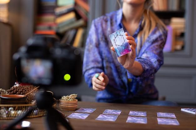 Sonderzeichen. selektiver fokus einer tarotkarte in weiblicher hand, während sie der kamera gezeigt wird the