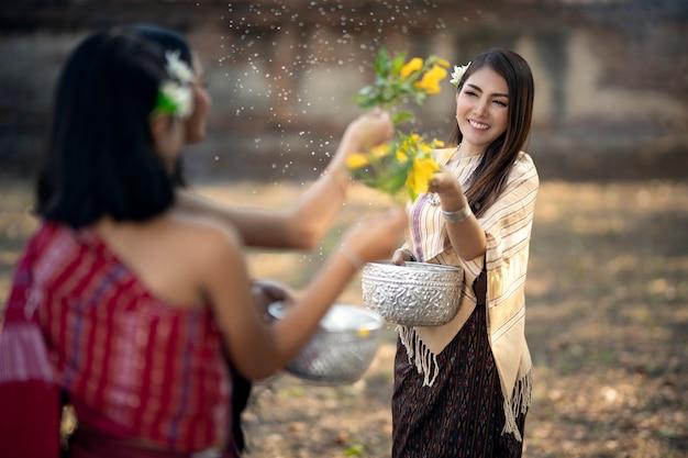 Songkran-festival das mädchen spritzt wasser und schließt sich der thailändischen neujahrstradition namens songkran day an.