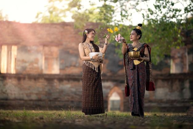 Songkran festival. eine frau in thailändischer tracht spritzt wasser auf das songkran-festival, eine thailändische nationaltradition, die als thailändisches neujahr gilt.