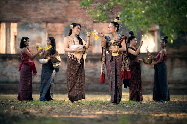 Songkran festival viele junge frauen in thailändischen trachten spritzen am songkran day wasser.