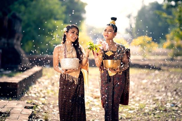 Songkran-festival zwei junge frauen spritzen wasser und nehmen an einer thailändischen neujahrstradition namens songkran day teil.