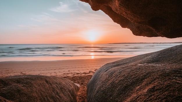 Sonne durch die klippen des strandes gesehen