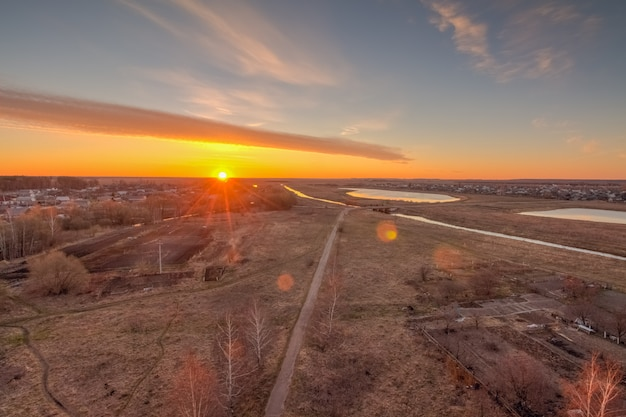 Sonne im morgengrauen am horizont über dem dorf