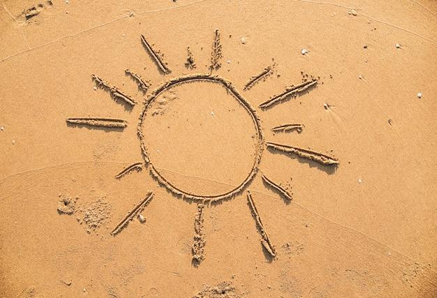 Sonne im sand gezeichnet